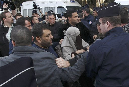 An unidentified veiled woman is taken away by plain clothed and uniformed police officers, flanked by a friend, center right, in Paris Monday, April  11, 2011. France&#39;s new ban on Islamic face veils was met with a burst of defiance Monday, as several women appeared veiled in front of Paris&#39; Notre Dame Cathedral and two were detained for taking part in an unauthorized protest. France on Monday became the world&#39;s first country to ban the veils anywhere in public. &#40;AP Photo&#47;Michel Euler&#41; <span class=meta>(AP Photo&#47; Michel Euler)</span>