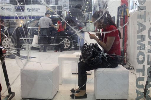 A vendor applies make-up as she sits behind bullet resistant glass during a security fair in Mexico City, Tuesday April 12, 2011. &#40;AP Photo&#47;Alexandre Meneghini&#41; <span class=meta>(AP Photo&#47; Alexandre Meneghini)</span>
