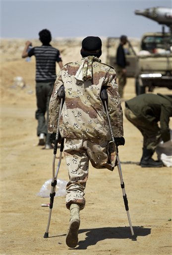 "<div class=""meta ""><span class=""caption-text "">Rebel fighter Abdul-Hakim Jinjan, 42, who lost his leg before the current conflict, walks on crutches to the pickup truck where he mans an anti-aircraft gun, on the outskirts of Ajdabiya, Libya Tuesday, April 12, 2011. (AP Photo/Ben Curtis) (AP Photo/ Ben Curtis)</span></div>"