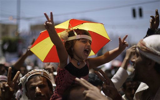 A Yemeni girl being held up by anti-government protestors shouts slogans during a demonstration demanding the resignation of Yemeni President Ali Abdullah Saleh, in Sanaa, Yemen, Tuesday, April 12, 2011. Yemeni President Ali Abdullah Saleh has welcomed mediation efforts by the regional bloc of oil-rich Arab nations even as he rejected their calls for him to step down, in a blow to regional efforts to resolve the weeks of turmoil that have been wracking this impoverished Arab nation. &#40;AP Photo&#47;Muhammed Muheisen&#41; <span class=meta>(AP Photo&#47; Muhammed Muheisen)</span>
