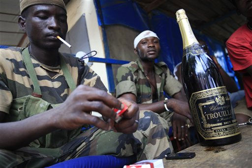 Republican forces soldiers relax around a bottle of champagne taken from the presidential residence one day earlier, as forces allied with Alassane Ouattara captured strongman Laurent Gbagbo, in Abidjan, Ivory Coast, Tuesday, April 12, 2011. President Ouattara called on all fighters to put down their arms now that the longtime strongman has been captured after his refusal to cede power sparked violence leaving bodies piled at morgues.&#40;AP Photo&#47;Rebecca Blackwell&#41; <span class=meta>(AP Photo&#47; Rebecca Blackwell)</span>