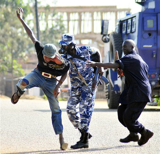 "<div class=""meta ""><span class=""caption-text "">Uganda Police beat  a protester, Thursday, April 14, 2011 in Kampala, Uganda. Witnesses in Uganda say police fired tear gas into a hospital during a skirmish with stone-throwing protesters.  A hospital worker, Mary Nabu, said patients were affected and that some mothers moved sick children from their beds to get away from the gas.  The police had surrounded opposition politician Kizza Besigye, who was walking to work to protest high gas prices. Ugandan youths allegedly began harassing the police.(AP Photo/Ronald Kabuubi) (AP Photo/ Ronald Kabuubi)</span></div>"