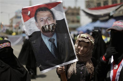 A female anti-government protestor holds up a poster of Yemeni President Ali Abdullah Saleh with a shoe stuck onto it, a symbolic cultural insult, during a demonstration demanding the resignation of  President Saleh, in Sanaa, Yemen, Sunday, April 17, 2011. Yemen&#39;s anti-government movement took up the issue of women&#39;s rights in the conservative Muslim nation on Saturday, as thousands of demonstrators seeking the ousting of the president denounced his comments against the participation of women in protest rallies. &#40;AP Photo&#47;Muhammed Muheisen&#41; <span class=meta>(AP Photo&#47; Muhammed Muheisen)</span>
