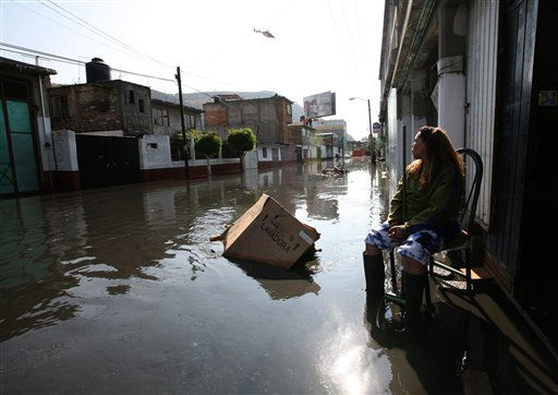 A woman sits in front of her house at a flooded area after heavy rains in Chalco, outskirts of Mexico City, Sunday, April 17, 2011. &#40;AP Photo&#47;Marco Ugarte&#41; <span class=meta>(AP Photo&#47; Marco Ugarte)</span>