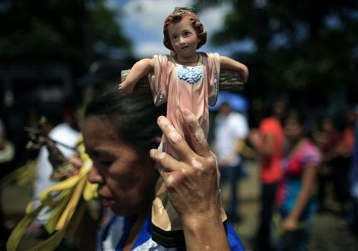 A woman carries a statue of the Child Christ before attending a Palm Sunday Mass in front of the Metropolitan Cathedral in Managua, Nicaragua, Sunday April 17, 2011.  &#40;AP Photo&#47;Esteban Felix&#41; <span class=meta>(AP Photo&#47; Esteban Felix)</span>