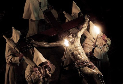Penitents carry an image of Christ on a cross, during the procession of the &#39;Cristo de la buena muerte&#39; brotherhood, during Holy Week in Zamora, northern Spain, in the early hours of Tuesday, April 19, 2011. Hundreds of processions take place throughout Spain during the Easter Holy Week. &#40;AP Photo&#47;I.Lopez&#41; <span class=meta>(AP Photo&#47; I.Lopez)</span>