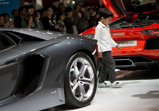 "<div class=""meta image-caption""><div class=""origin-logo origin-image ""><span></span></div><span class=""caption-text"">A child plays on a rotating platform displaying Lamborghini sport cars at the 14th Shanghai International Automobile Industry Exhibition in Shanghai, China Wednesday, April 20, 2011. Global automakers unveiled ambitious expansion plans for China on Tuesday, targeting the country's newly prosperous drivers as the industry struggles to recover from Japan's tsunami. (AP Photo/Andy Wong) (AP Photo/ Andy Wong)</span></div>"