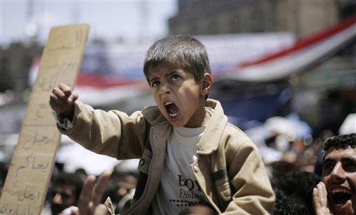 "<div class=""meta ""><span class=""caption-text "">A Yemeni boy lifted up by anti-government protestors, shouts slogans during a demonstration demanding the resignation of  of Yemeni President Ali Abdullah Saleh in Sanaa, Yemen, Wednesday, April 20, 2011. A Yemeni opposition activist said a gunmen on motorcycles opened fire at hundreds of demonstrators camped out overnight in a western port city, killing one and wounding several protesters. (AP Photo/Muhammed Muheisen) (AP Photo/ Muhammed Muheisen)</span></div>"