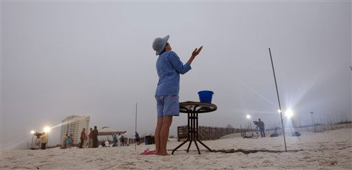 Donna McCormick of Gulf Shores, Ala., prays during a prayer vigil in Orange Beach, Ala., Wednesday, April 20, 2011 for those who suffered following the Deepwater Horizon incident.  Eleven people died a year ago when the oil rig exploded. &#40;AP Photo&#47;Dave Martin&#41; <span class=meta>(AP Photo&#47; Dave Martin)</span>