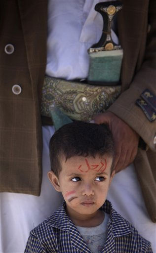 A Yemeni boy with writing on his face in Arabic which reads, &#34;Leave&#34; stands with his father during a demonstration demanding the resignation of Yemeni President Ali Abdullah Saleh in Sanaa, Yemen, Thursday, April 21, 2011. The head of a regional Gulf Arab political group was in Yemen on Thursday to lead a fresh effort to find a way out for the country&#39;s embattled president who has faced two months of mass protests demanding his ouster. &#40;AP Photo&#47;Muhammed Muheisen&#41; <span class=meta>(AP Photo&#47; Muhammed Muheisen)</span>