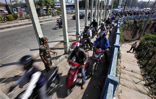 A soldier allows a limited number of motorcycles to proceed as others wait for their turn to fill up their motorcycles outside an army-run gas station in Katmandu, Nepal, Thursday, April, 21, 2011. Nepal imports all its oil products from India but supply has stopped because the state-owned company has failed to pay its bills. &#40;AP Photo&#47;Gemunu Amarasinghe&#41; <span class=meta>(AP Photo&#47; Gemunu Amarasinghe)</span>