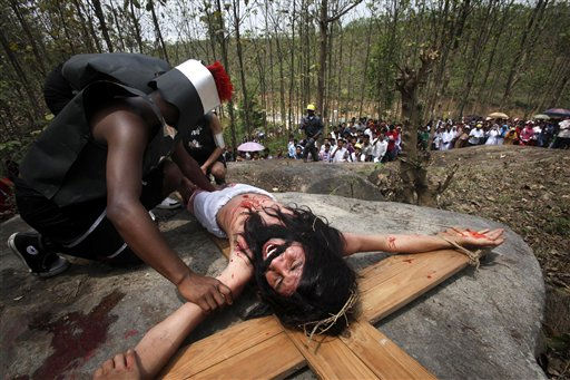 A devotee dressed as Jesus Christ reenacts the crucifixion as others pray on the occasion of Good Friday, in Gauhati, India, Friday, April 22, 2011. &#40;AP Photo&#47; Anupam Nath&#41; <span class=meta>(AP Photo&#47; Anupam Nath)</span>