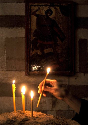 "<div class=""meta ""><span class=""caption-text "">Woman's hand lights a candle during an Easter liturgy in 10th century convent church of St. Mary in Veljusa, near southeastern Macedonia's town of Strumica, early Sunday, April 24, 2011. (AP Photo/Boris Grdanoski) (AP Photo/ BORIS GRDANOSKI)</span></div>"