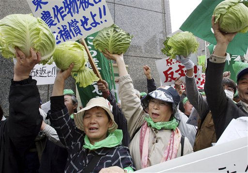 "<div class=""meta image-caption""><div class=""origin-logo origin-image ""><span></span></div><span class=""caption-text"">Farmers, mostly from Fukushima Prefecture where the tsunami crippled Fukushima Dai-ichi plant is located, hold up cabbages during a protest in front of the Tokyo Electric Power Co. (TEPCO) headquarters in Tokyo Tuesday, April 26, 2011. More than 200 farmers affected by radiation spewing from the nuclear plant staged a demonstration to demand that TEPCO pays them adequate compensation for loss of income caused by having to leave their farms, or for having produced withdrawn from the market due to contamination fears. (AP Photo/Koji Sasahara) (AP Photo/ Koji Sasahara)</span></div>"