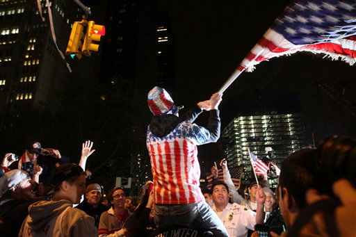 "<div class=""meta ""><span class=""caption-text "">Perched on another's shoulders, Ryan Burtchell, of the Brooklyn borough of New York, center, waves an American flag over the crowd as they respond to the news of Osama Bin Laden's death early Monday morning May 2, 2011 by ground zero in New York.   President Barack Obama announced Sunday night that Osama bin Laden was killed in an operation led by the United States.  (AP Photo/Erika Rich/Daily Texan) (AP Photo/Tina Fineberg) (AP Photo/ Tina Fineberg)</span></div>"