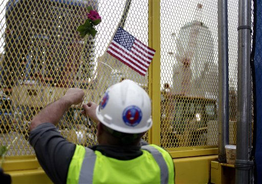 "<div class=""meta ""><span class=""caption-text "">Construction worker Paddy Garvey affixes an American flag to a fence at ground zero in New York, Monday, May 2, 2011. Osama bin Laden, the face of global terrorism and architect of the Sept. 11, 2001, attacks, was killed in a firefight with elite American forces in Pakistan on Monday, May 2, 2011 then quickly buried at sea. (AP Photo/Seth Wenig) (AP Photo/ Seth Wenig)</span></div>"