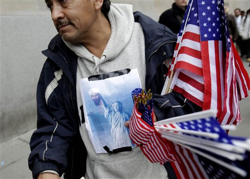 A poster showing the Statue of Liberty holding the head of Osama bin Laden is taped to Francisco Miranda&#39;s clothes as he sells flags at ground zero in New York, Monday, May 2, 2011. Joyous at the release of a decade&#39;s frustration, Americans streamed to the site of the World Trade Center, the gates of the White House and smaller but no less jubilant gatherings across the nation to celebrate the death of Osama bin Laden ? cheering, waving flags and belting the national anthem. &#40;AP Photo&#47;Seth Wenig&#41; <span class=meta>(AP Photo&#47; Seth Wenig)</span>