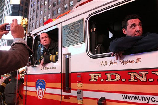 FDNY firefighter Scott Hickey, left, and a fellow firefighter who did not give his name, sit in a fire truck parked in New York&#39;s Times Square as a crowd gathers in reaction to the news of Osama Bin Laden&#39;s death early Monday morning May 2, 2011. A plaque with names of Ladder 4 firefighters who lost their lives in the Sept. 11 attacks, the house that Hickey belongs to, is seen on the side of the truck.  &#40;AP Photo&#47;Tina Fineberg&#41; <span class=meta>(AP Photo&#47; Tina Fineberg)</span>
