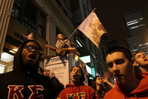 Simi Lampert, of New York, seated atop a phone booth, waves a banner and sings with others gathered by ground zero in New York as they react to the news of Osama Bin Laden&#39;s death early Monday morning May 2, 2011.  President Barack Obama announced Sunday night, May 1, 2011, that Osama bin Laden was killed in an operation led by the United States.  &#40;AP Photo&#47;Tina Fineberg&#41; <span class=meta>(AP Photo&#47; Tina Fineberg)</span>