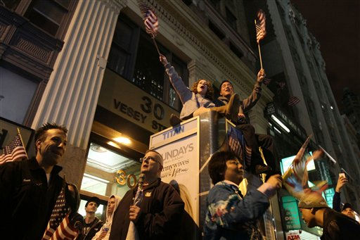 Waving American flags as they sit atop a phone booth, Simi Lampert, left, and Ryan Chung, both of New York, gather with others by ground zero in New York as they react to the news of Osama Bin Laden&#39;s death early Monday morning May 2, 2011. President Barack Obama announced Sunday night, May 1, 2011, that Osama bin Laden was killed in an operation led by the United States.  &#40;AP Photo&#47;Tina Fineberg&#41; <span class=meta>(AP Photo&#47; Tina Fineberg)</span>