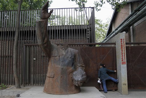 A woman tries to open the door of a metal gate next to a statue of a headless red guard in Beijing Wednesday, May 4, 2011. &#40;AP Photo&#41; <span class=meta>(AP Photo&#47; Anonymous)</span>