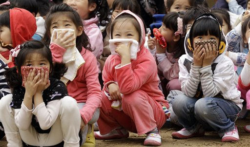 South Korean elementary school students covering their mouths gather on the ground after escaping from their classrooms during an earthquake drill in Seoul, South Korea, Wednesday, May 4, 2011. Students throughout the nation practiced drills ranging from fire to terror attacks and earthquake as part of the annual drills called a Safe Korea Exercise. &#40;AP Photo&#47; Lee Jin-man&#41; <span class=meta>(AP Photo&#47; Lee Jin-man)</span>