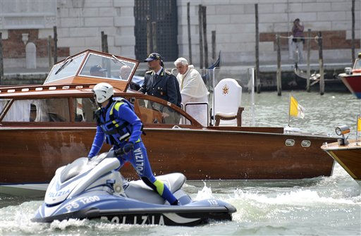 Pope Benedict XVI crosses the Grand Canal on a wooden boat in Venice, Italy, Sunday, May 8, 2011. Pope Benedict XVI celebrated an open-air Mass on Sunday for 300,000 faithful in Venice, the spiritual highlight of his two-day pastoral visit to the lagoon city. It is the first papal visit to the city since John Paul II plied the canals in a gondola 26 years ago. The visit was held under tight security, with helicopters flying overhead and the pope flanked by his personal security corps. Most traffic in the area of the Mass was blocked, but worshippers were not required to go through metal detectors or have their bags checked as they streamed into the park. &#40;AP Photo&#47;Luigi Costantini&#41; <span class=meta>(AP Photo&#47; Luigi Costantini)</span>