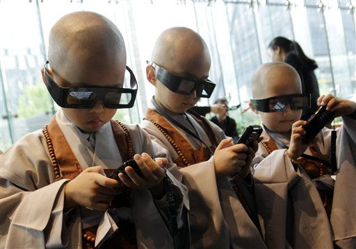 Shaven-headed young boys wearing 3-D glasses touch smart phones at SK Telecom Ubiquitous Museum in Seoul, South Korea, Monday, May 9, 2011. A group of children entered a temple, the main temple of Korean Buddhism&#39;s Chogye Order, to experience a monk&#39;s life for a month to celebrate Buddha&#39;s birthday on May 10.&#40;AP Photo&#47; Lee Jin-man&#41; <span class=meta>(AP Photo&#47; Lee Jin-man)</span>