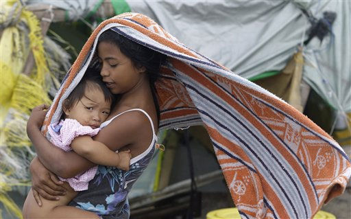 "<div class=""meta image-caption""><div class=""origin-logo origin-image ""><span></span></div><span class=""caption-text"">A Filipino girl carries a baby as strong winds blow at a temporary relocation area in Navotas, north of Manila, Philippines on Monday May 9, 2011. Tropical storm Aere threatened the Philippines' agricultural north Monday after pummeling the eastern coast and the capital with fierce winds and rain that sparked floods and landslides, officials said. (AP Photo/Aaron Favila) (AP Photo/ Aaron Favila)</span></div>"