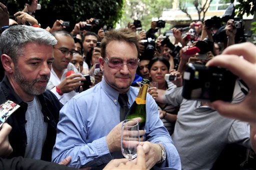 Holding a champagne bottle, the lead singer of the Irish rock band U2, Bono, center, greets fans as he celebrates his 51th birthday in Mexico City, Tuesday, May 10, 2011. U2 will perform in concert in Mexico City on May 11, 14 and 15. &#40;AP Photo&#41; <span class=meta>(AP Photo&#47; Anonymous)</span>