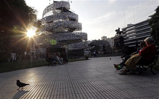 People sit in front of a tower made of some 30.000 books in different languages, named &#34;Babel Tower&#34;, at San Martin Square, in Buenos Aires, Argentina, Wednesday, May 11, 2011. Created by artist Marta Minujin, from Argentina, the tower was inaugurated on May 11 and will be open to visitors from May 12 to 28. &#40;AP Photo&#47;Natacha Pisarenko&#41; <span class=meta>(AP Photo&#47; Natacha Pisarenko)</span>