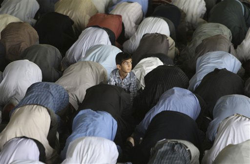 A Iranian boy looks on as worshippers perform their Friday prayer, at the Tehran University campus, in Tehran, Iran, Friday, May 13, 2011. &#40;AP Photo&#47;Vahid Salemi&#41; <span class=meta>(AP Photo&#47; Vahid Salemi)</span>