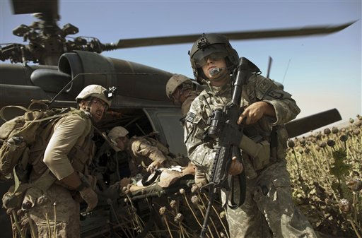 "<div class=""meta ""><span class=""caption-text "">US Army flight medic SPC. Daniel Miller, right, stands guard as United States Marines place a colleague wounded in an IED strike into a waiting medevac helicopter from the US Army's Task Force Lift ""Dust Off"", Charlie Company 1-214 Aviation Regiment at a ""hot"" landing zone in Sangin, in the volatile Helmand Province of southern Afghanistan, Friday, May 13, 2011. (AP Photo/Kevin Frayer) (AP Photo/ Kevin Frayer)</span></div>"