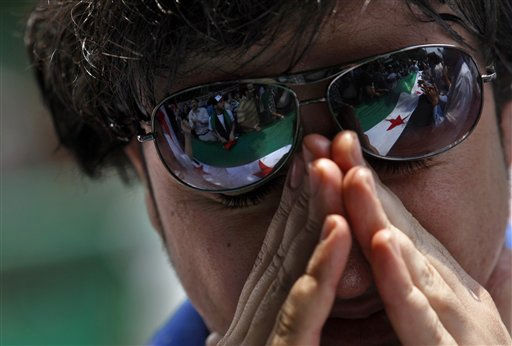 A Syrian protester weeps as others, seen reflected in his sunglasses, chant slogans and hold Syrian flags during a demonstration demanding that Syria&#39;s President Bashar Assad step down, in front of the Arab League headquarters building in Cairo, Egypt, Sunday, May 15, 2011. Hundreds of Syrians fled to neighboring Lebanon to escape a violent crackdown against an anti-government uprising that has claimed the lives of more than 800 civilians, Lebanese security officials and a leading human rights group said. &#40;AP Photo&#47;Khalil Hamra&#41; <span class=meta>(AP Photo&#47; Khalil Hamra)</span>