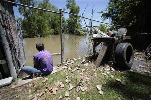 John Harrington sits in the back yard of his friend&#39;s house as he watches the rising waters of the Atchafalaya River approach the property in Melville, La., Monday, May 16, 2011. &#40;AP Photo&#47;Gerald Herbert&#41; <span class=meta>(AP Photo&#47; Gerald Herbert)</span>