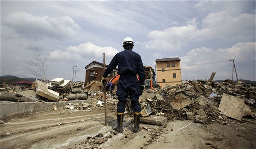 A police officer stands watch a mass clean up operation in an area devastated by the March 11 earthquake and tsunami in Kesennuma,  Tuesday, May 17, 2011.&#40;AP Photo&#47;Junji Kurokawa&#41; <span class=meta>(AP Photo&#47; Junji Kurokawa)</span>