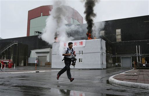 An employee runs to sound off alarms during an emergency drill at Taiwan Power Co.&#39;s number 2 nuclear power plant in Wanli district, Taipei county, northeastern Taiwan, Tuesday, May 17, 2011. &#40;AP Photo&#47;Wally Santana&#41; <span class=meta>(AP Photo&#47; Wally Santana)</span>
