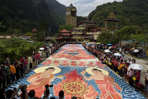 "<div class=""meta ""><span class=""caption-text "">Devotees wishing to rejuvenate their spirits unfurl a giant canvas measuring 60-meter by 12-meter canvas painting of Sakyamuni Buddha out in the sun to dry in Ipoh, Malaysia Tuesday, May 17, 2011. (AP Photo/Vincent Thian) (AP Photo/ Vincent Thian)</span></div>"