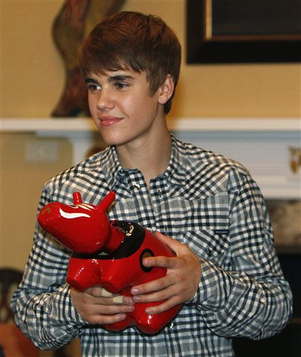 Canadian singer-songwriter Justin Bieber holds &#34;akabeko,&#34; a Japanese traditional toy red cow, presented to him during a meeting with schoolchildren evacuated from areas devastated by the March 11 earthquake and tsunami, at U.S. ambassador&#39;s residence in Tokyo, Wednesday, May 18, 2011. &#40;AP Photo&#47;Shizuo Kambayashi&#41; <span class=meta>(AP Photo&#47; Shizuo Kambayashi)</span>