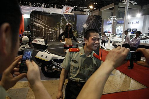A Chinese paramilitary police man reacts as he poses for photos with a model and a police motorcycle at an exhibition on police equipment and anti-terror technologies held in Beijing, China, Thursday, May 19, 2011. &#40;AP Photo&#47;Ng Han Guan&#41; <span class=meta>(AP Photo&#47; Ng Han Guan)</span>