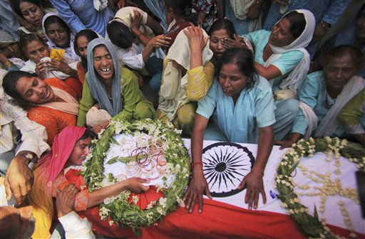 Sushma, left with hands on coffin, wife of slain paramilitary soldier Raspal, mourns near her husband&#39;s coffin at Nagrota village, about 23 kilometers &#40;14 miles&#41; from Jammu, India, Thursday, May 19, 2011. A senior police official said seven paramilitary soldiers were killed in the eastern Indian state of Chhatisgarh in a land mine explosion they believe was triggered by Maoist rebels. &#40;AP Photo&#47;Channi Anand&#41; <span class=meta>(AP Photo&#47; Channi Anand)</span>