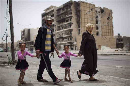 A family walks in Tripoli Street, the center of fighting between the rebels and Moammar Gadhafi forces in Misrata, Libya, Sunday, May 22, 2011. The European Union established formal diplomatic contact with the Libyan opposition on Sunday by opening an office in the rebel stronghold of Benghazi. &#40;AP Photo&#47;Rodrigo Abd&#41; <span class=meta>(AP Photo&#47; Rodrigo Abd)</span>