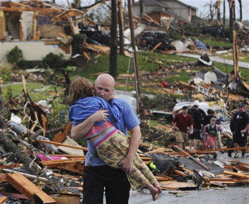 A man carries a young girl who was rescued after being trapped with her mother in their home after a tornado hit Joplin, Mo. on Sunday evening, May 22, 2011. The tornado tore a path a mile wide and four miles long destroying homes and businesses. &#40;AP Photo&#47;Mike Gullett&#41; <span class=meta>(AP Photo&#47; Mike Gullett)</span>