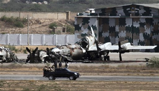 Pakistani troops gather next to a burnt plane inside the naval aviation base following an attack by militants in Karachi, Pakistan, Monday, May 23, 2011. Pakistani commandos were close to regaining control of a naval base Monday as they hunted for any last holdouts among a team of Taliban militants who attacked and occupied the facility for 15 hours, destroying two U.S.-supplied planes and killing 12 security officers. &#40;AP Photo&#47;Shakil Adil&#41; <span class=meta>(AP Photo&#47; Shakil Adil)</span>