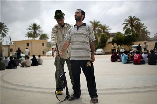 A rebel instructor tells a man how to stand in a military position during a training exercise in Misrata, Libya, Tuesday, May 24, 2011. According to rebel military authorities, after six days of military training, new recruits are ready to go to fight on the front line against Moammar Gadhafi forces. &#40;AP Photo&#47;Rodrigo Abd&#41; <span class=meta>(AP Photo&#47; Rodrigo Abd)</span>