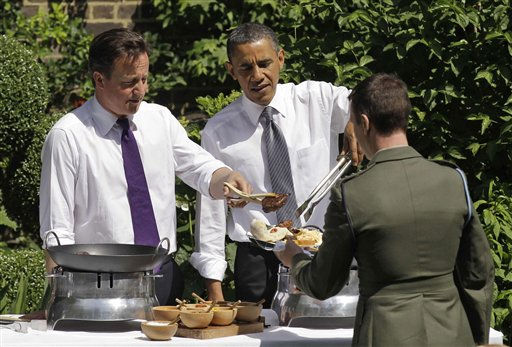 Britain&#39;s Prime Minister David Cameron, left, and U.S. President Barack Obama serve food to a member of the military during a barbecue in the garden of 10 Downing Street in London, Wednesday, May 25, 2011.  The barbecue Wednesday, where Cameron, Obama and their wives served food, was attended by members of the military from the UK and the U.S.  &#40;AP Photo&#47;Matt Dunham-Pool&#41; <span class=meta>(AP Photo&#47; Matt Dunham)</span>