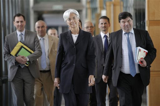 French Finance Minister Christine Lagarde, center, arrives surrounded by members of her staff for a press conference, in Paris, Wednesday May 25, 2011. Lagarde on Wednesday launched her bid to lead the International Monetary Fund, a candidacy that would put the first woman in charge of the scandal-rocked fund but increases tensions with developing nations who want one of their as head. &#40;AP Photo&#47;Thibault Camus&#41; <span class=meta>(AP Photo&#47; Thibault Camus)</span>