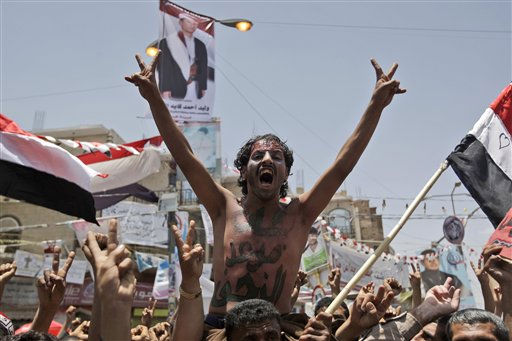 An anti-government protestor lifted by other demonstrator, shouts slogans during a demonstration demanding the resignation of Yemeni President Ali Abdullah Saleh, in Sanaa, Yemen, Monday, May 30, 2011. Yemeni warplanes carried out airstrikes Monday on a southern town seized by hundreds of Islamic militants over the weekend, witnesses said, as the political crisis surrounding the embattled president descended into more bloodshed. &#40;AP Photo&#47;Hani Mohammed&#41; <span class=meta>(AP Photo&#47; Hani Mohammed)</span>