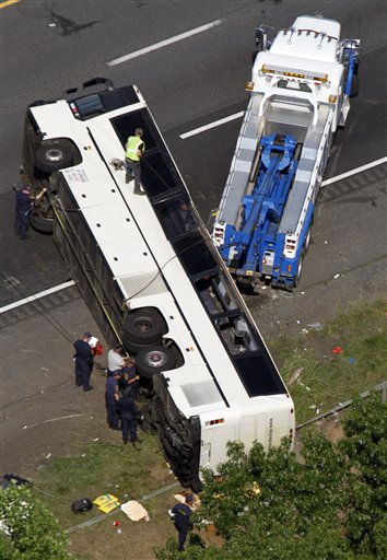 Rescue personnel work on a bus that overturned Tuesday, May 31, 2011, in Bowling Green, Va. The commercial tour bus went off Interstate 95 in Virginia and flipped on its roof before dawn Tuesday, killing four people and injuring many more, state police said. &#40;AP Photo&#47;Steve Helber&#41; <span class=meta>(AP Photo&#47; Steve Helber)</span>