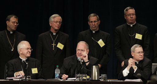 "<div class=""meta image-caption""><div class=""origin-logo origin-image ""><span></span></div><span class=""caption-text"">With newly appointed bishops standing behind him, Archbishop Timothy Dolan, front-row center, of New York, president of the United States Conference of Catholic Bishops, speaks Wednesday, June 15, 2011, in Bellevue, Wash. At front-row left is Archbishop Joseph Kurtz, of Louisville, KY, vice president of the USCCB, and at front-row right is Monsignor David Malloy, the general secretary of the USCCB. (AP Photo/Ted S. Warren) (AP Photo/ Ted S. Warren)</span></div>"